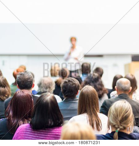 Business and entrepreneurship symposium. Female speaker giving a talk at business meeting. Audience in the conference hall. Rear view of unrecognized participant in audience. Square composition.