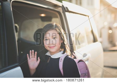 Asian girl in student uniform going to school by car and waving goodbye