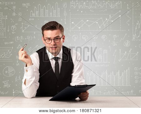 Young handsome businessman sitting at a desk with white graphs and calculations behind him