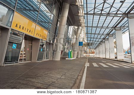 Entrance to airport building is located under canopy. It is near road