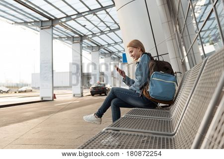 Happy young woman looking at mobile while sitting on bus-stop near airdrome