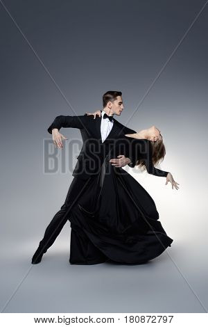 Couple of professional dancers performing tango. Beautiful young people in love dancing on a date. Studio shot.