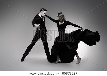 Black-and-white portrait of professional dancers performing tango. Beautiful young people in love dancing on a date. Studio shot.