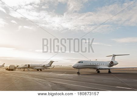 Various planes situating at landing strip under clear morning sky before starting flight