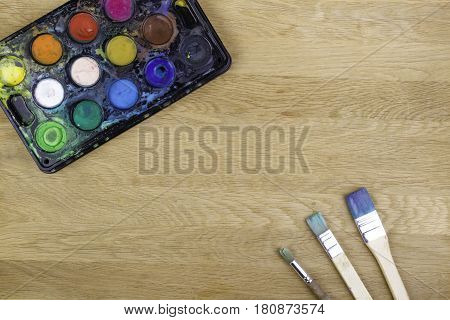 Watercolors paints and brushes on wooden surface. Top view