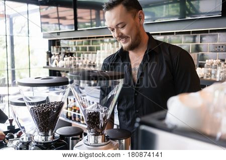 Happy young man preparing espresso from fresh roasted coffee beans while working as barista in a modern coffee shop
