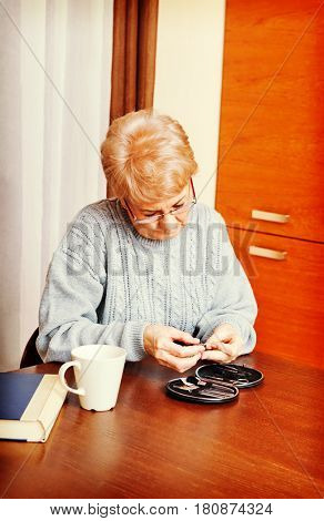 Senior woman sitting at the desk and cutting fingers nails
