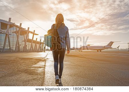 Female tourist walking at plane parking lot. She keeping bag. Journey concept