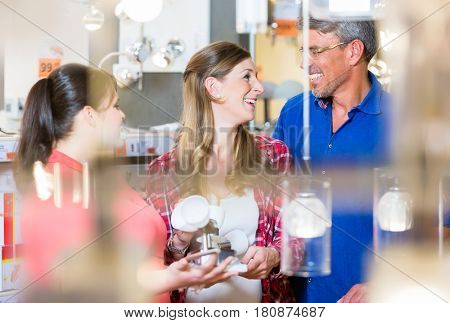 Clerk giving advice about lamps to couple, woman and man, in electrical goods department of hardware store