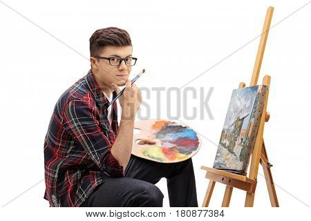 Teenage painter with a paintbrush and a palette sitting in front of a canvas and looking at the camera isolated on white background