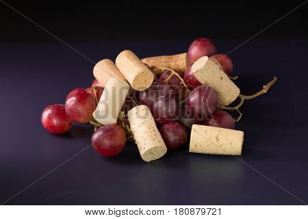 Many Wine Corks And A Vintage Cork Screw And Red Grape On A Dark Background
