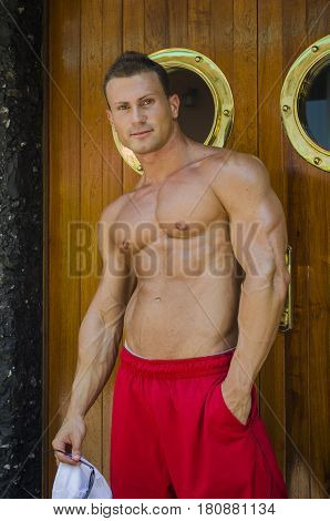 Muscular shirtless young man by ship porthole, standing and looking at camera