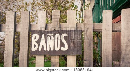 Wooden slat fence with a banos sign
