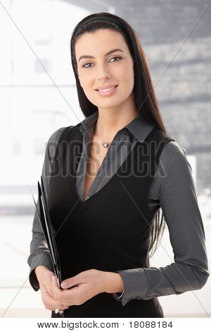 Ritratto di smart office worker donna in piedi in ufficio con la cartella documenti, sorridente.?