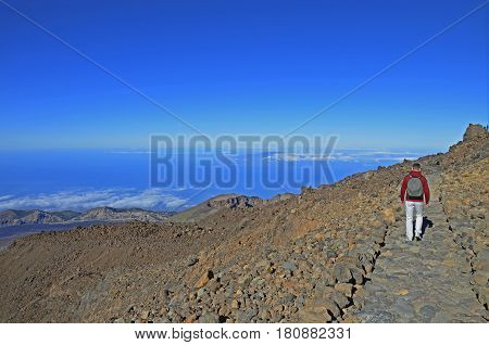 A man trekking on the Teide volcano Tenerife with a view to the ocean and clouds