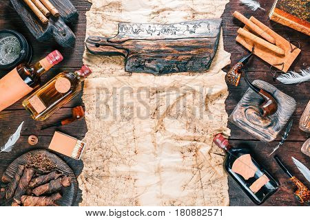 Frame of smoking pipes, cigars, tobacco and brandy bottles on dark wood desk and old paper. Western style. Wooden signboard as title. Top view