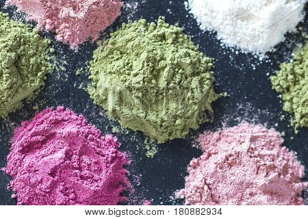 Various colorful superfood powders on dark background. Healthy food supplements detox concept. Top view