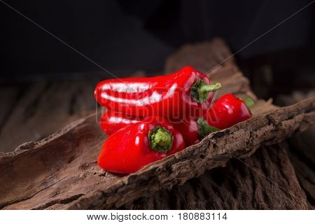 Red chilly pepper on wooden black background. Red hot chili peppers. Domestic cultivation extra hot chilli burn.