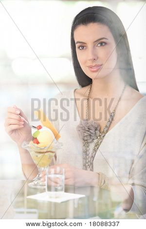 Happy woman having ice cream cup at cafe table, smiling, picture through window.?