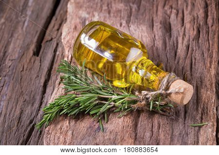 rosemary Herbs and Medicinal herbs. fresh rosemary bunch and oil on wooden background.