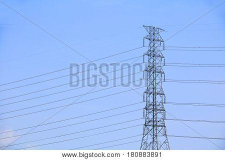 High voltage power pole on sky background