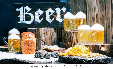 Mugs of beer, bread loaf, dried fish and potato chips on raw wood pub counter with natural stumps and oak barrel. Wood signboard with text 'Beer'