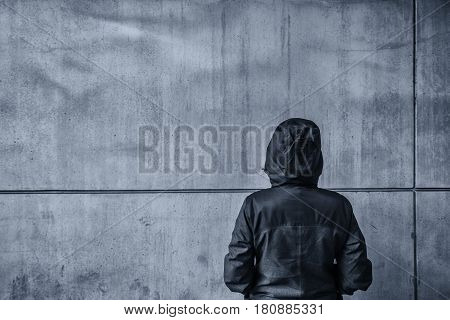 Unrecognizable hooded female person facing concrete wall as insurmountable obstacle young adult woman in urban surrounding confronting problems and difficulties in life. poster