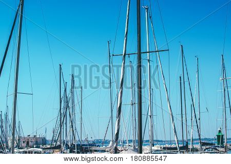 Sailboat masts in harbor against blue sky summer holiday vacation abstract background