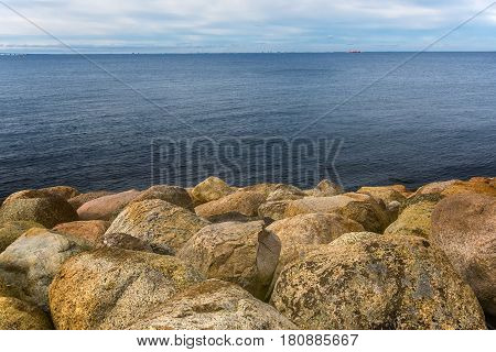 Large rocks on sea shore water's edge seascape on cold winter day