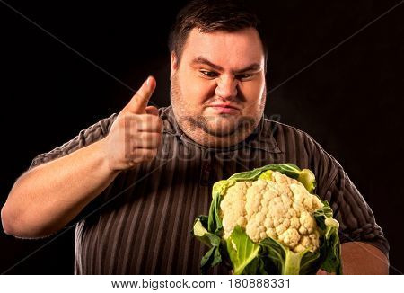 Diet fat man eating healthy food . Healthy breakfast with vegetables cauliflower for overweight person. Male trying to lose weight. Concept on black background.