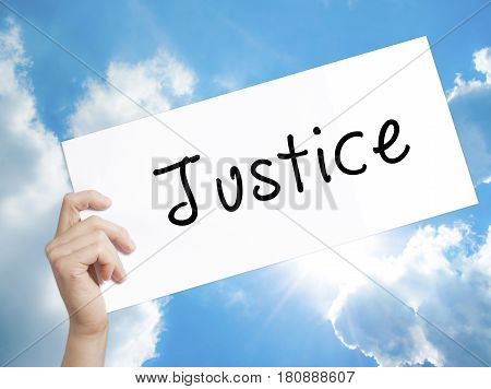 Justice Sign on white paper. Man Hand Holding Paper with text. Isolated on sky background. Business concept. Stock Photo