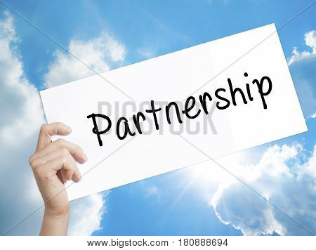 Partnership Sign on white paper. Man Hand Holding Paper with text. Isolated on sky background. Business concept. Stock Photo