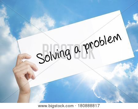 Solving A Problem Sign On White Paper. Man Hand Holding Paper With Text. Isolated On Sky Background