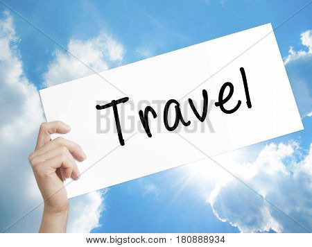 Travel Sign on white paper. Man Hand Holding Paper with text. Isolated on sky background. Business concept. Stock Photo