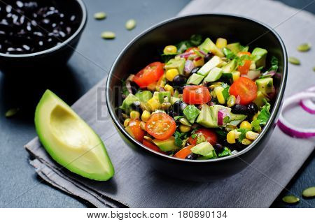 Black beans corn avocado red onion tomato salad with lime dressing.