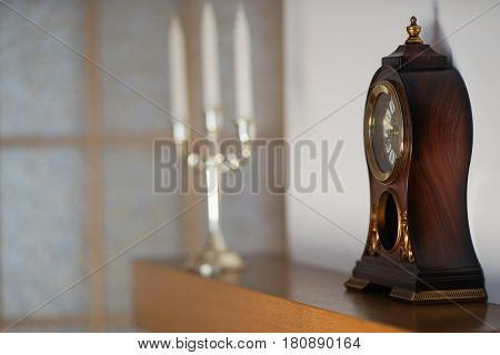 mantel clock on a background of white walls with a chandelier in the background