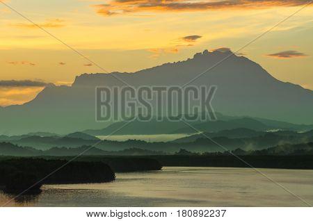 Sunrise sky,river and misty layer majestic mountain Kinabalu,Sabah,Borneo.