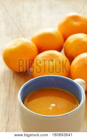 orange squeeze in cup and tangerine on wooden board