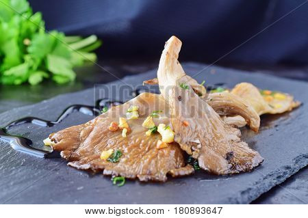 Fried oyster mushrooms with garlic, parsley in a balsamic glaze on a black background. Healthy eating concept