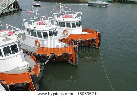 Three tug boats Orange stationed on a dock in the river Tagus in Lisbon Portugal