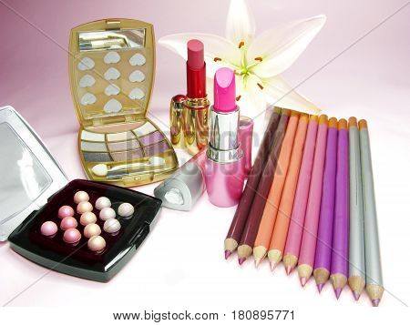 lipsticks eye shadows pencils lip gloss and lily on background