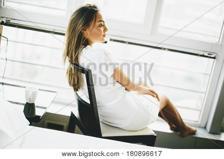 Young Woman Sitting And Dreaming On A Chair By The Window In Her Nightgown