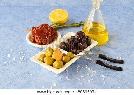 A set of dishes of greek cuisine: olives, sun dried tomatoes, lemon, glass jar with olive oil. Traditional Greek food. Mediterranean lifestyle.