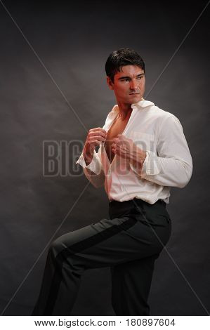 The handsome man is unbuttoning his shirt.