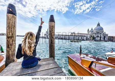 Blonde girl having fun sitting on the pier in Venice. Back view