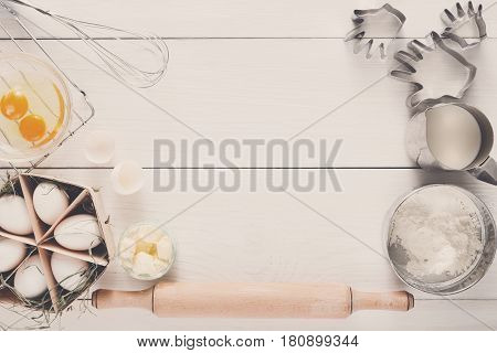 Baking background. Cooking ingredients for dough and pastry, eggs yolks, flour and cookie cutter on white rustic wood. Top view with copy space, mockup for menu, recipe or culinary classes.