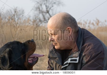 man and rottweiler dog face to face**Note slight blurriness, best at small sizes. poster