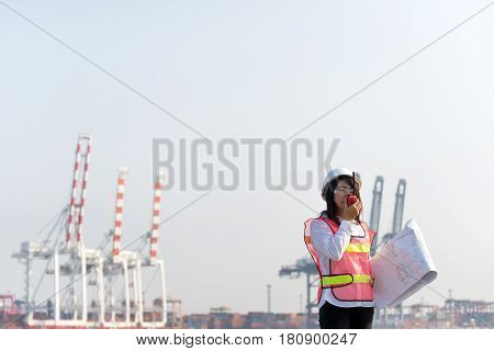 The women engineer working with container Cargo freight ship in shipyard at dusk for Logistic Import Export background