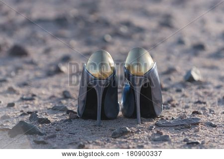 fashion and glamour. fashionable pair of female shoes high heels golden and silver on ground or soil of sand and rocky stones desert surface on sunny day outdoors on grey sandy background.