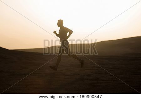 sprinting sport and marathon. man runner or fit male athlete running in desert sand dune at mountain in sun ray at sunset sunrise outdoor on white sky background. healthy lifestyle success workout